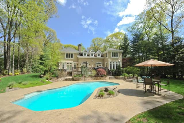 This Dimmig Road home features a heated pool and outdoor spa — right here in Upper Saddle River.