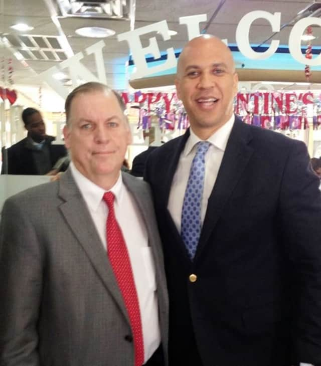 Neighbors Helping Neighbors founder John Fugazzie stands with New Jersey Sen. Cory Booker, in 2014.
