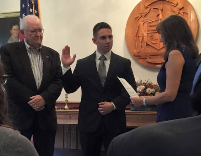 Weston's newest police officer Jon Marsili is sworn in by First Selectman Gayle Weinstein, right, during a ceremony with Police Commission Chairman Bill Brady.