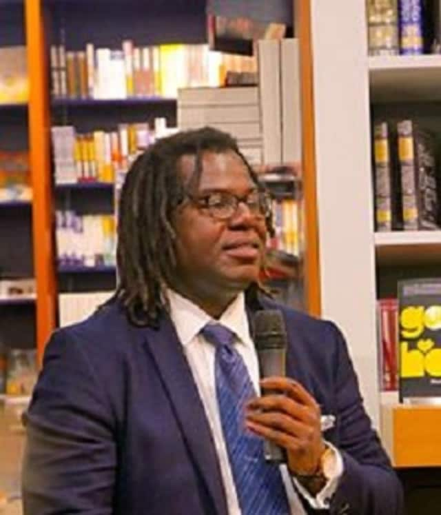 """One of two book clubs meeting at the Scarsdale Public Library this month will be discussing Dimitry Léger's debut novel, """"God Loves Haiti."""" Leger is pictured at a book-signing in Zurich."""