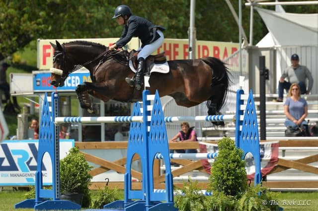 Leslie Howard soars to victory with Quadam on the final day of competition at Old Salem Farm's Spring Horse Shows. Photograph by The Book.