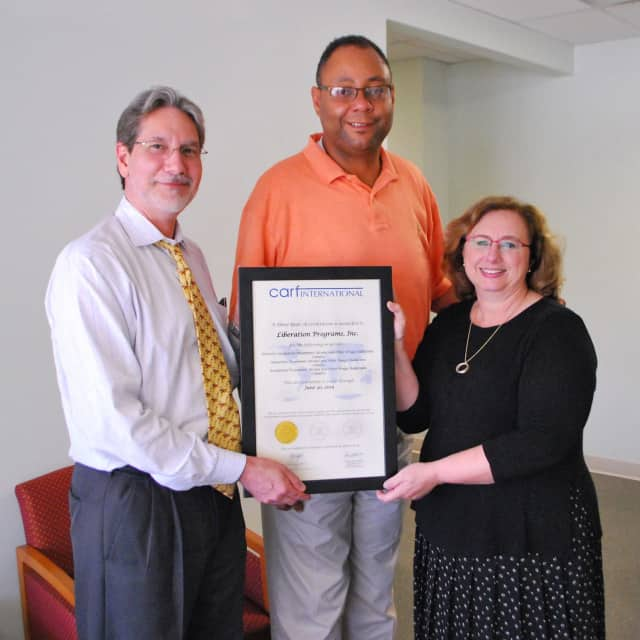 Liberation Programs' Cary Ostrow, chief administrative officer; Alan Mathis, president and CEO; and Dr. Patti Juliana, chief program officer, display three-year certification from CARF International.