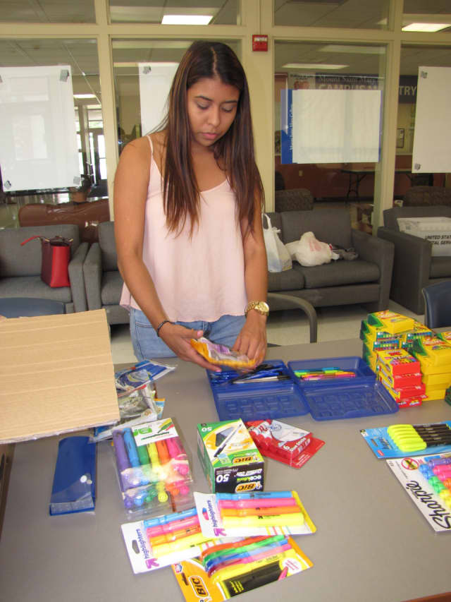 Mount St. Mary College senior Gabriela Monroy. of Mamaroneck, a human services major, helps stuff book bags with school supplies on Friday, Sept. 4.