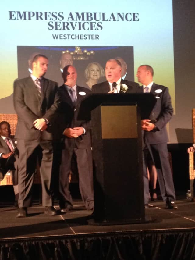 Mike Minerva, president of Empress Ambulance Services in Yonkers, surrounded by his family as he accepts an award as one of Westchester's most outstanding family-owned businesses.