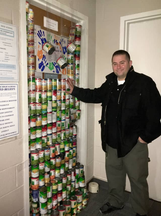 Nick DiPaolo stands in front of his office door, which was barricaded with cans of food by his high school colleagues.