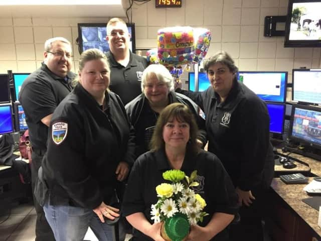 Eileen Maschak (with flowers) is congratulated by colleagues Saturday as she retires as a Ramapo police dispatcher. Behind her are, l-r: Jennifer Orfini, Mary Steinberger, and Angela Cahill. In the back row are, l-r: Brett Levine and Tom Stevens.