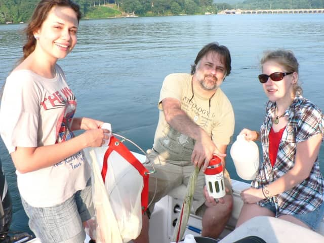 Professor of environmental and biological sciences Mitch Wagener collecting zebra mussel samples with former Western Connecticut State University students Bruna Oliviera, left, and Catrina Morga.