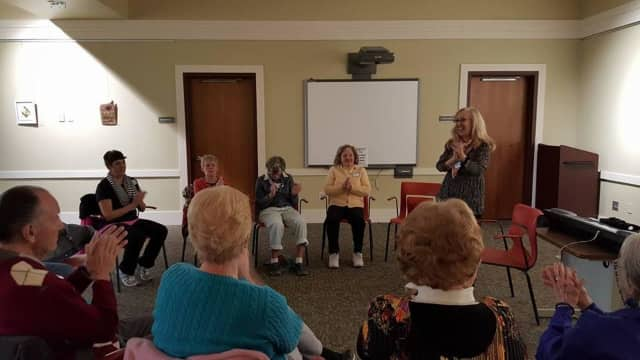 Certified Music Therapist Melinda Burgard leads a rhythmic clapping activity during a recent Music Social Program at the Albert Wisner Public Library in Warwick.