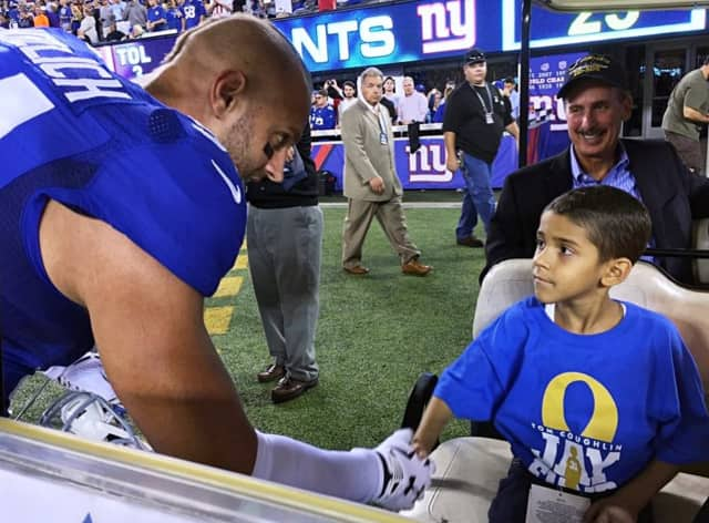New York Giant Mark Herzlich shakes hands with Jhosua, a pediatric cancer patient supported by the Tom Coughlin Jay Fund Foundation. That organization will receive a portion of Muscle Maker Grill's proceeds on Saturday.