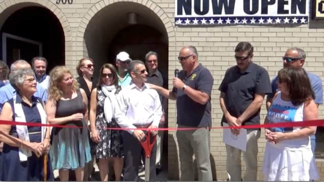 Mayor Frank Catalina helps Charles Newman cut the ribbon on his new business.