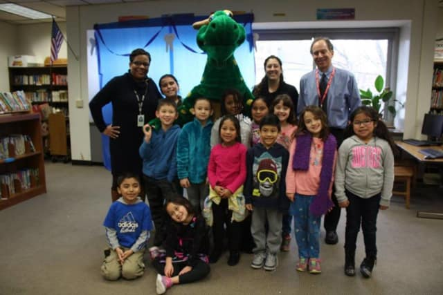 Oakside Elementary School students pose with Fidelis Insurance Company's trademark Fidelis dinosaur during the school's first annual Dental Health Fair on Feb. 25.
