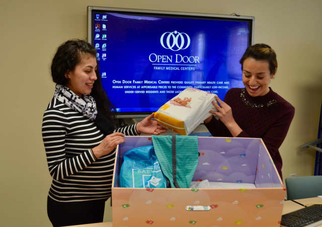 """At the Open Door Family Medical Center in Ossining on March 7, Community Coordinator Alaina Betancourt (right) reviews the contents of
