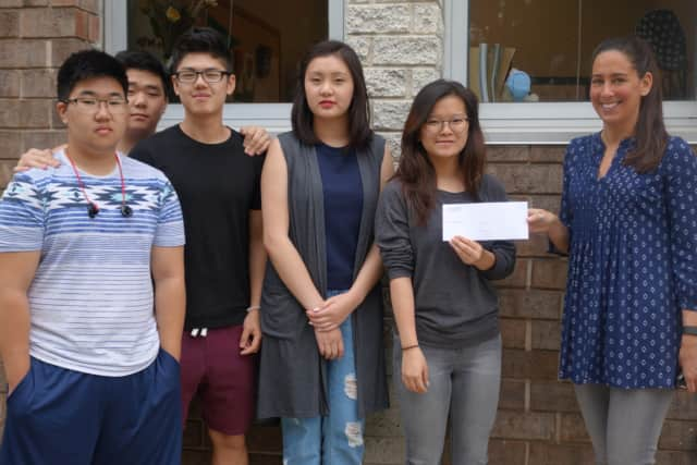 Abraham Kim, Edwin Kwon, Andrew Zheng, Dechen Choden, and Jasmine Oh of Tenafly High School's IMPACT club hand a $300 check to Keri Diamond of Care Plus.