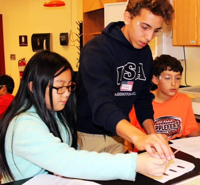 An Ossining High School student works with younger students to spur interest in science. Eight students from Ossining High School are semifinalists in the 2016 Intel Science Talent Search competition.