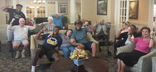 Pace University football players Jorge Geronimo, Adam Wooten and Prince Unaegbu are shown with some of the residents at Atria Briarcliff Manor. The athletes ran an exercise program this past school year at the facility.