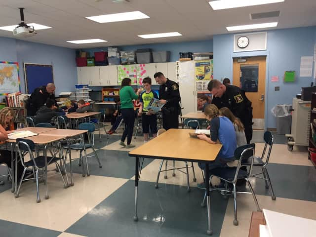 """Students at the Pierre Van Cortlandt Middle School in Croton-on-Hudson take part in a  """"Mannequin Challenge"""" to illustrate acts of kindness. They were helped out by D.A.R.E. officer Robert Leonard and two of his colleagues."""