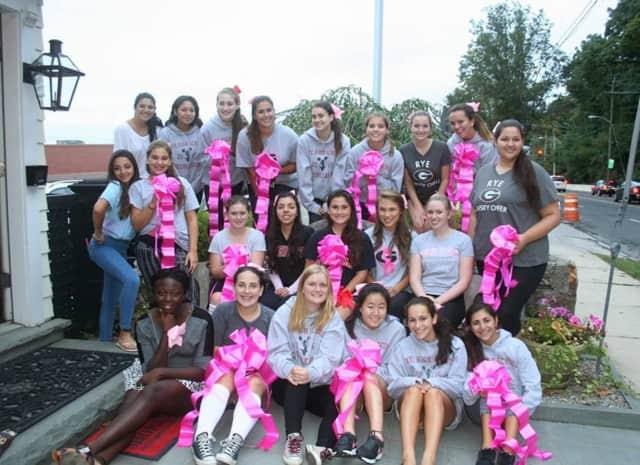 Rye cheerleaders with pink ribbons.