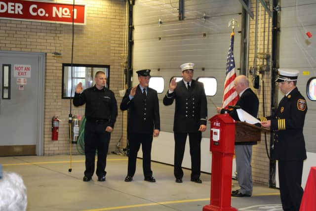 First Selectman Mike Tetreau (second from right) administers the oath of office to (left to right) Firefighter Justin Crawford, Lieutenant Kevin Polcer and Assistant Chief Roger Caisse.