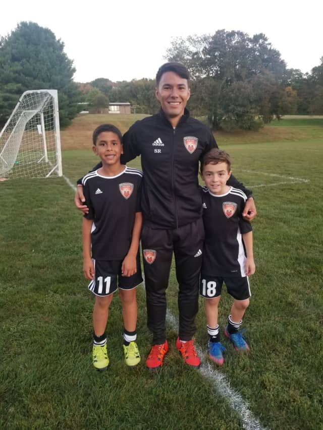 Soccer standouts Kunar, left, and Scalera, right, pose with Coach Rojas.