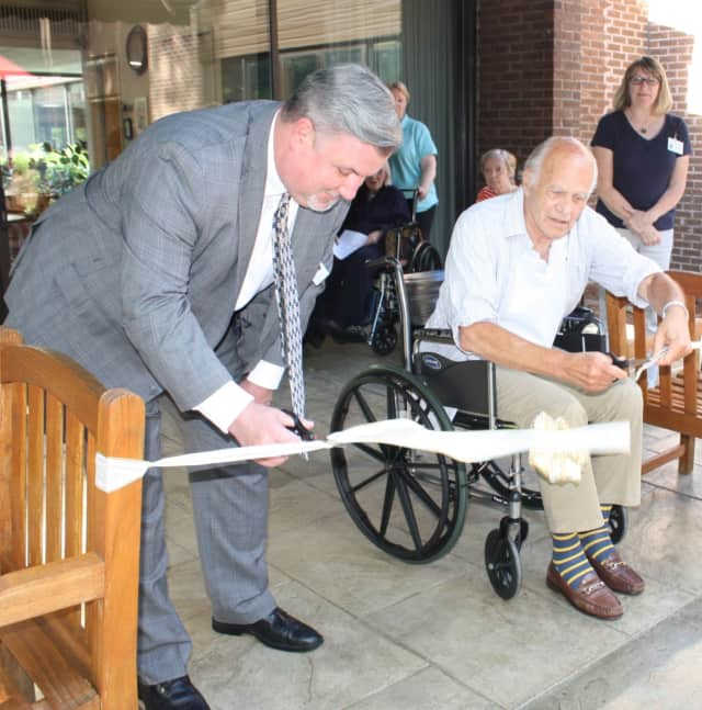 Together, Waveny LifeCare Network's CEO, Bill Piper, left and Resident Council president, Gerry Roberts, open the new therapeutic patio on the organization's  main campus.
