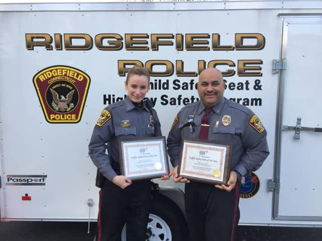 Ridgefield police Officers Victoria Ryan and Lou Caba show off the American Automobile Association (AAA) awards that they received for their contributions to traffic safety.