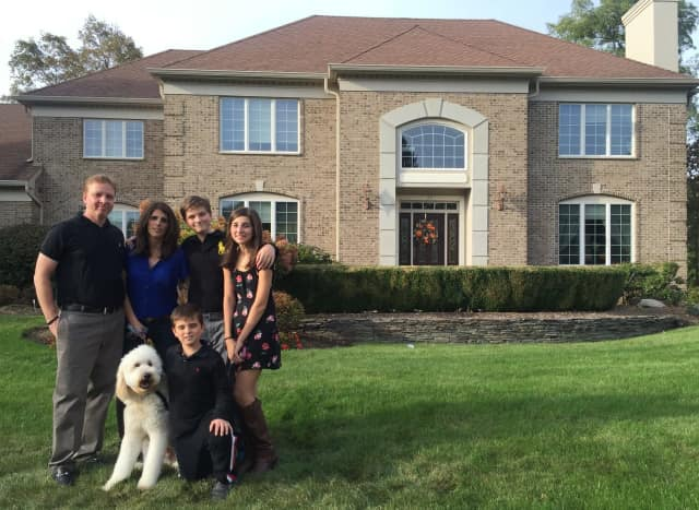 Nancy Smith and her family pose in front of their home at Rio Vista Estates in Mahwah.