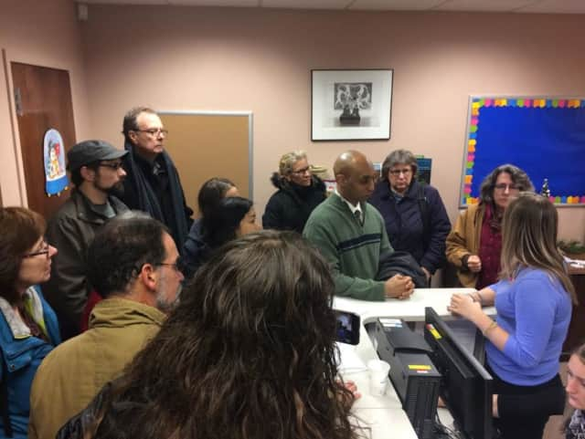 Michael Lockett of Rockland United, center in green sweater, talks with Allison Biasotti, regional director for Charles Schumer, at the senator's Peekskill office Tuesday. The group was concerned over his voting to confirm several Cabinet picks.