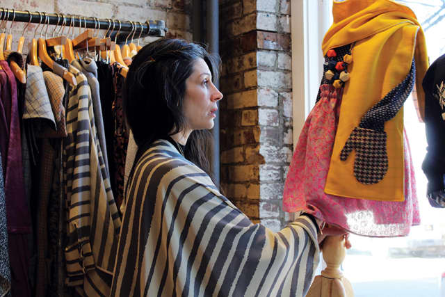 Stephanie Doucette rearranges a mannequin displaying an outfit from Petite Doucette, her children's collection. Photograph by Danielle Renda.