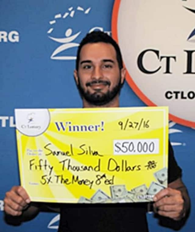 Samuel Silva of Fairfield, the owner of a Greenwich pizza shop, shows off his winnings.