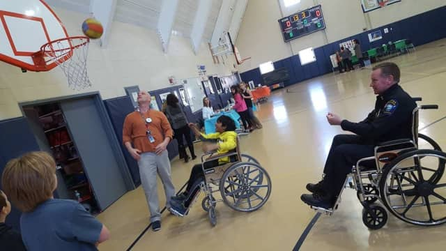 """Easton Police Chief Tim Shaw tries his hand at wheelchair basketball during """"Diversity Day"""" at Samuel Staples Elementary School."""