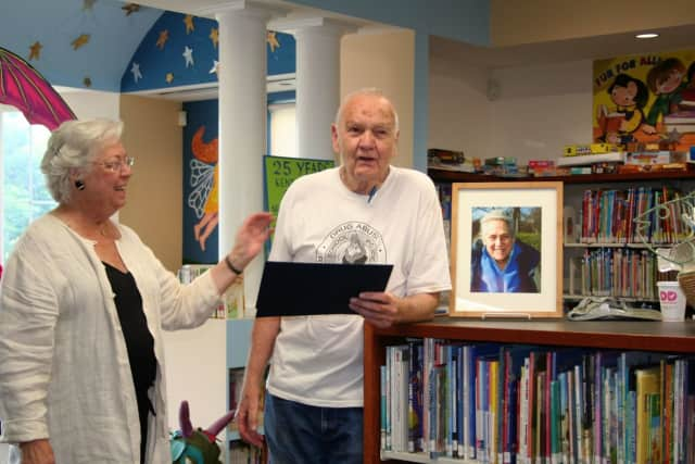 Sandy Galef presents a proclamation to Jim Baker as the children's room was dedicated to Wilma Baker.