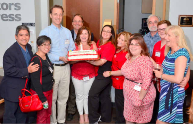 AFC/Doctors Express owner Brad Radulovacki (in blue shirt), staff and guests celebrate the urgent care center's one-year anniversary in Stamford on June 17.