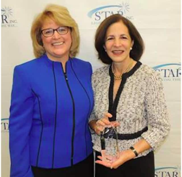 """Katie Banzhaf, executive director of STAR, Inc. (left) presents the """"Humanitarian of the Year"""" award to State Representative Gail Lavielle."""