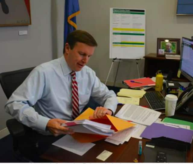 U.S.Senator Chris Murphy stuffs the 450 'Fed Up' responses into an envelope to send to U.S. Department of Transportation Secretary Anthony Foxx.