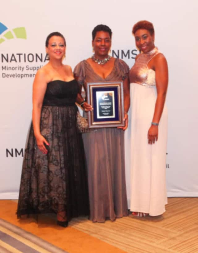 Valerie Cooper (center), founder and owner of Picture That, with her award from the National Minority Supplier Development Council. At right is Kimberlyn McKoy, Picture That's curator; at left is Joset Wright-Lacy, president of NMSDC.