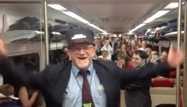 Metro-North conductor Bob McDonough tries his hand at musical conducting as the Yale Glee Club rides his train last week.