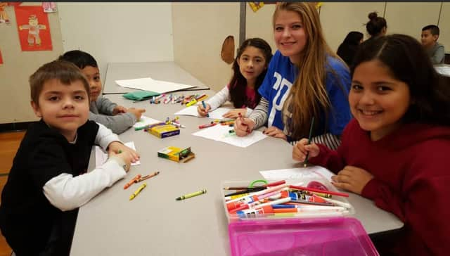 Students from the Roxbury and Julia A. Stark elementary schools in Stamford and their high school mentors make holiday cards and posters for clients of a local hospice organization