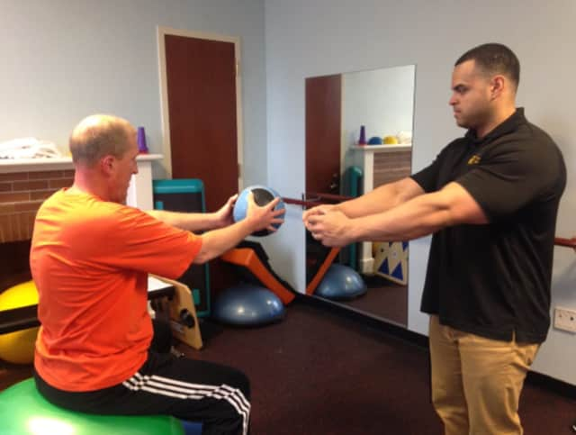 Facility Supervisor Ken Figueroa, right, instructs a member on how to perform an abdominal exercise at the Burke Rehabilitation Center's Adult Fitness Center.