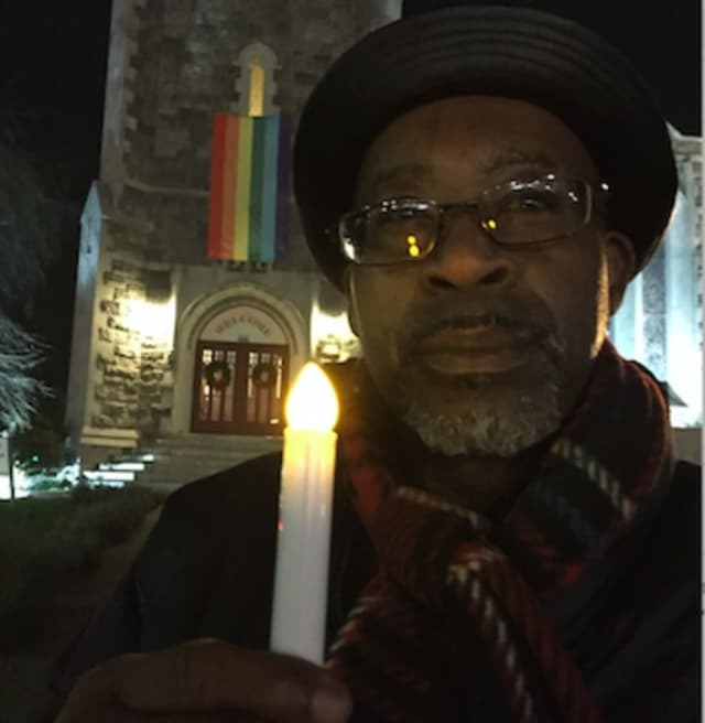 Johnathan Bati'e holding a candle was one of the participants in a service to mark National Homeless Persons Memorial Day on Monday. It was held at the First Congregational Church in Stamford.