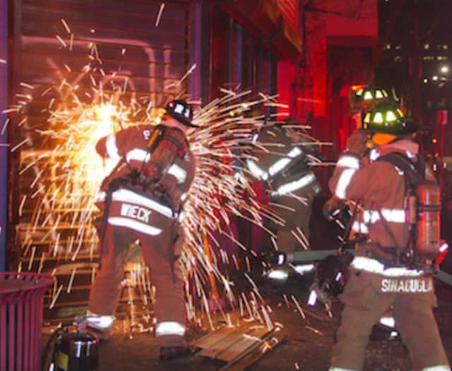 Stamford firefighters work to gain entry to 97 Manhattan St. They were able to douse a fire in the second story of the abandoned building Monday night.