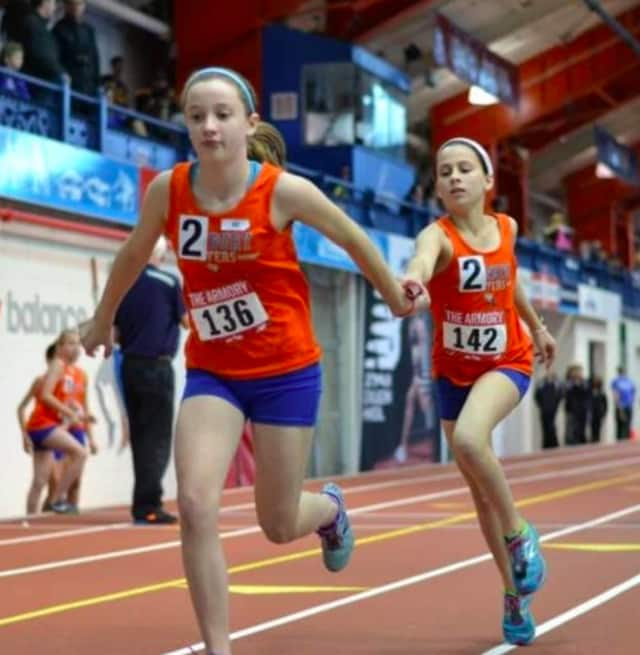 Danbury Flyers girls exchange the baton during a relay race at the meet. The Danbury Flyers recently competed in two track and field meets.