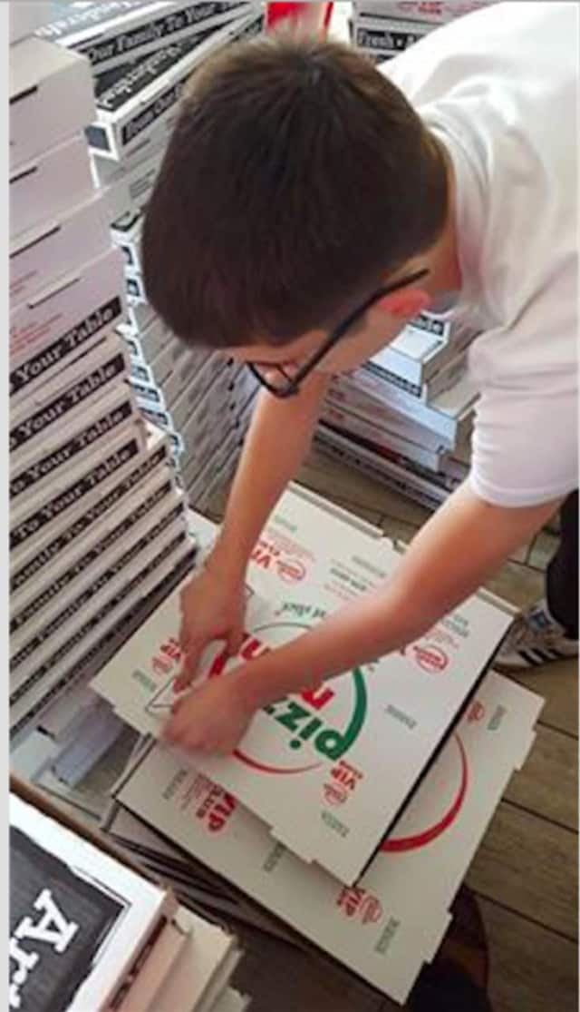 Members of the Garfield Prevention Coalition put awareness stickers on pizza boxes to remind parents that it is illegal to serve alcohol to minors.