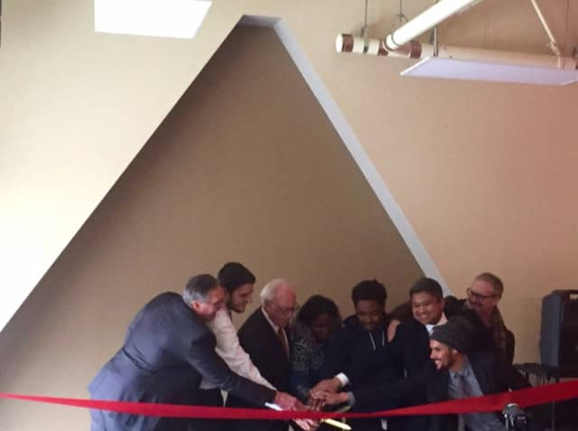 Purchase College President Thomas Schwarz (center) at a ribbon-cutting ceremony with students and faculty, dedicating a new multicultural center at Fort Awesome dormitory.