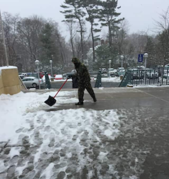A man goes to work cleaning snow and slush from the Greenwich Library's front entrance on Monday.