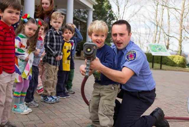Firefighter/Paramedic Nick Paproski shows Ridgefield Academy students how to use a firehose.