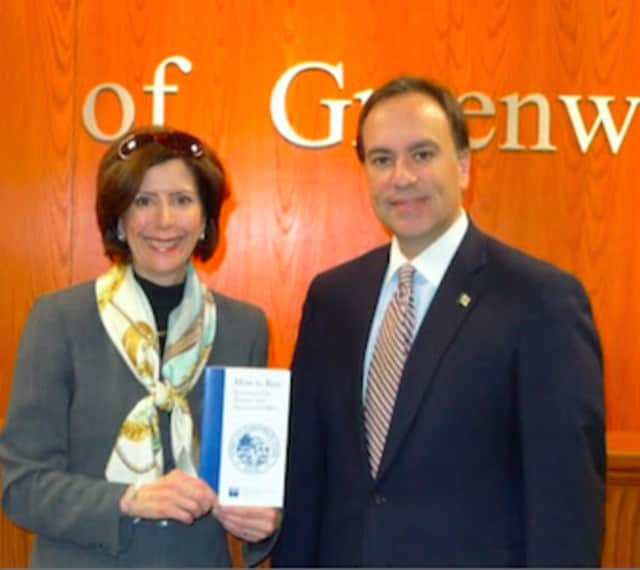 """Deirdre Kamlani presents First Selectman Peter Tesei with the updated version of """"How to Run for Greenwich Elective and Appointive Offices."""""""