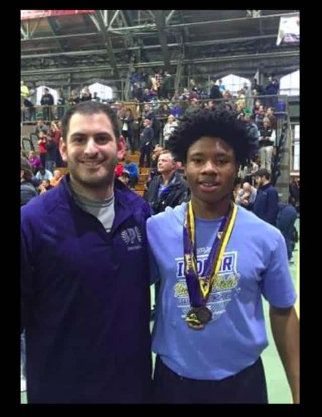 Justin Johnson, right, a student in the Pelham school district, medaled twice at the New York State Indoor Track meet. Johnson is pictured with coach Greg Kopstein.