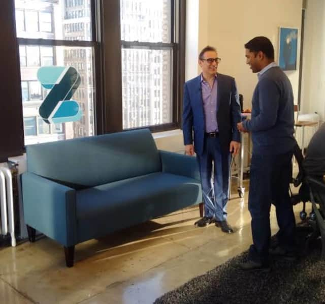 New Rochelle's Rudy Callegari, left, talks to a Zootly employee in his New York office. Callegari started the business after getting frustrated in finding a mover for the blue loveseat to his right.