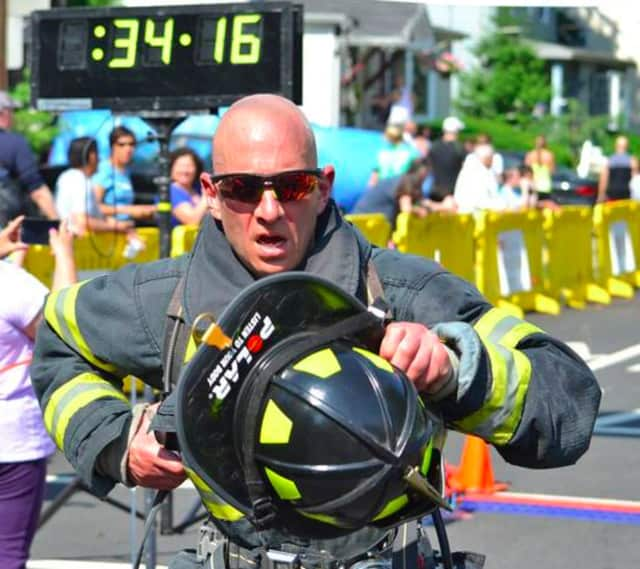 A New Milford firefighter crosses the finish line at a previous 5K Run.