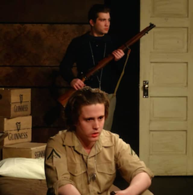 "The titular character of Brendan Behan's quirky, dark comedy, ""The Hostage,"" playing in Curtain Call's Dressing Room Theatre, Stamford, March 17 thru April 3 is played by Byron O'Hanlon (seated). Seen here guarding the hostage is Justin Lockwood."